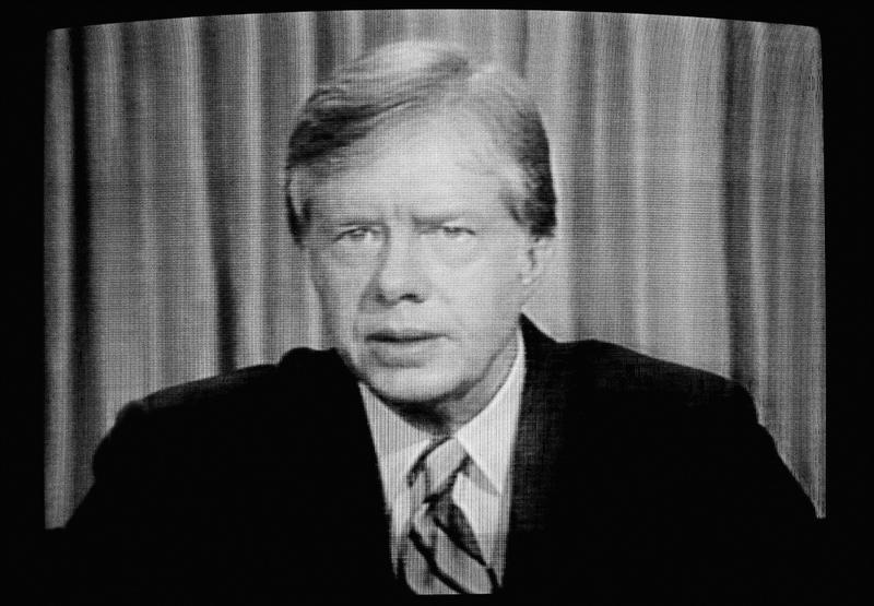 Former President Jimmy Carter is shown on a video screen as he addresses the nation on the failed attempt to rescue the American hostages in Iran, April 25, 1980.