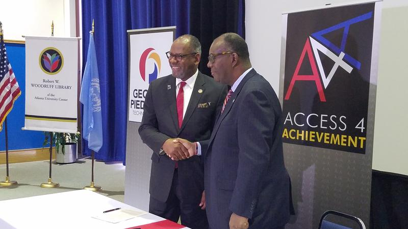 The president of Georgia Piedmont Technical College, Jibari Simami and Clark Atlanta University president Ronald Johnson shake hands after a new agreement was signed between schools.