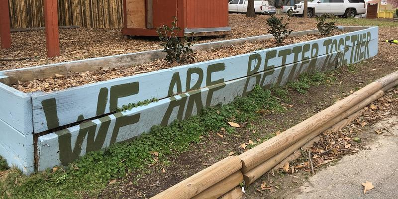 A raised flower bed in Mattie Freeland Park, with the words 'We Are Better Together' painted on the side.