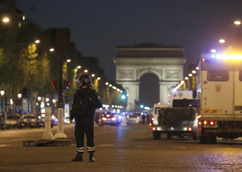 A police officer stands guard Thursday night near the Arc de Triomphe in Paris following an attack that left a police officer dead and two officers seriously wounded. The gunman was shot dead by police.