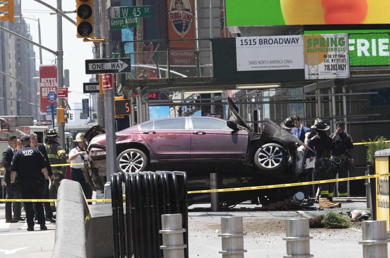 A car rests on a security barrier in New York's Times Square after driving through a crowd of pedestrians, with at least one fatality and more than 20 other injuries.
