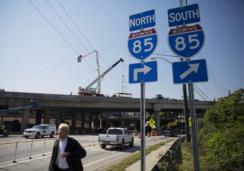 Construction crews work on the I-85 bridge earlier this week. Local news media report drivers began using northbound lanes about 7 p.m. Friday. The southbound lanes are expected to reopen by Sunday.