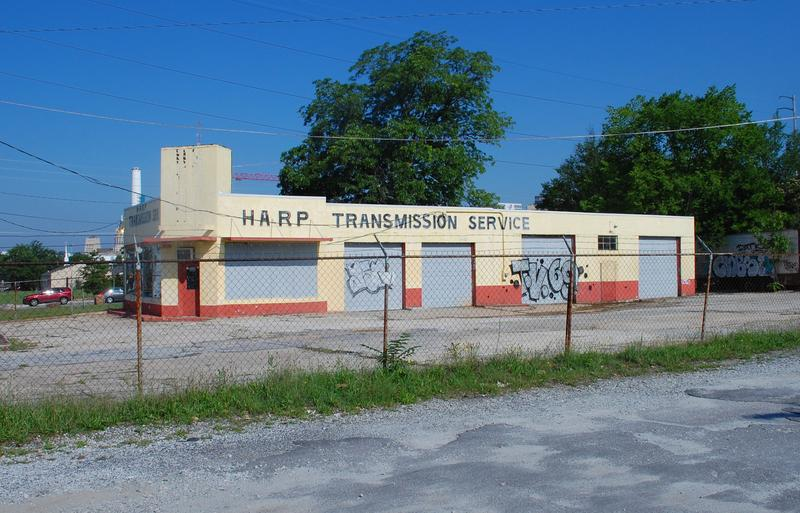 "The site where the auto shop Harp Transmission once operated sits within a stretch of land slated to be greenspace. Local developers want to redevelop the space as a mixed-use ""pavilion in the park."""