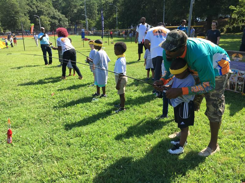 Kendall Newson, founder of Teach a Child to Fish, shows kids how to cast in Washington Park.