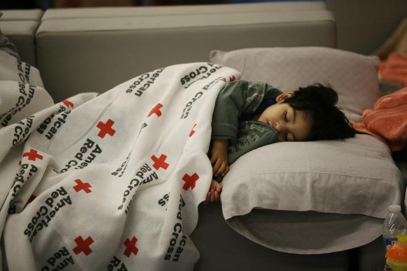 Malachia Medrano, 2, sleeps Tuesday at the George R. Brown Convention Center that has been set up as a shelter for evacuees escaping the floodwaters in Houston. Organizations in Atlanta are working to help in the storm-impacted area.