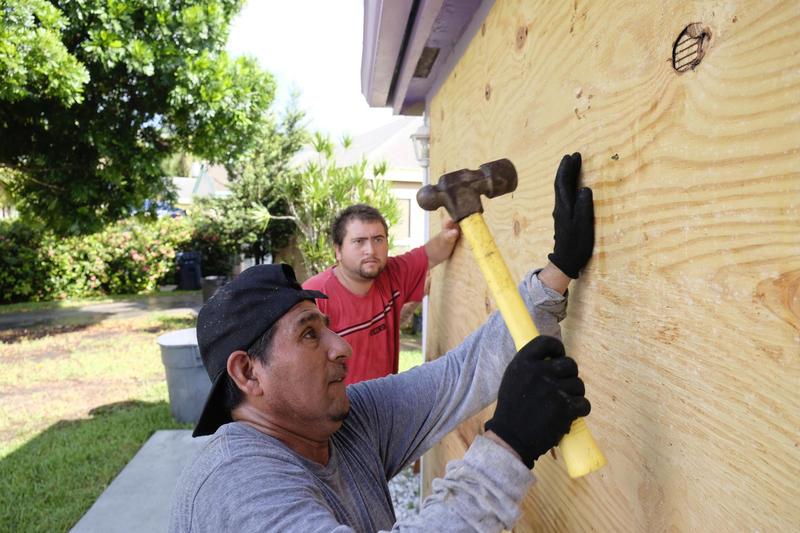 Pedro Reimundo installs wood shutters on a home in Florida City, Florida, on Friday ahead of Hurricane Irma.