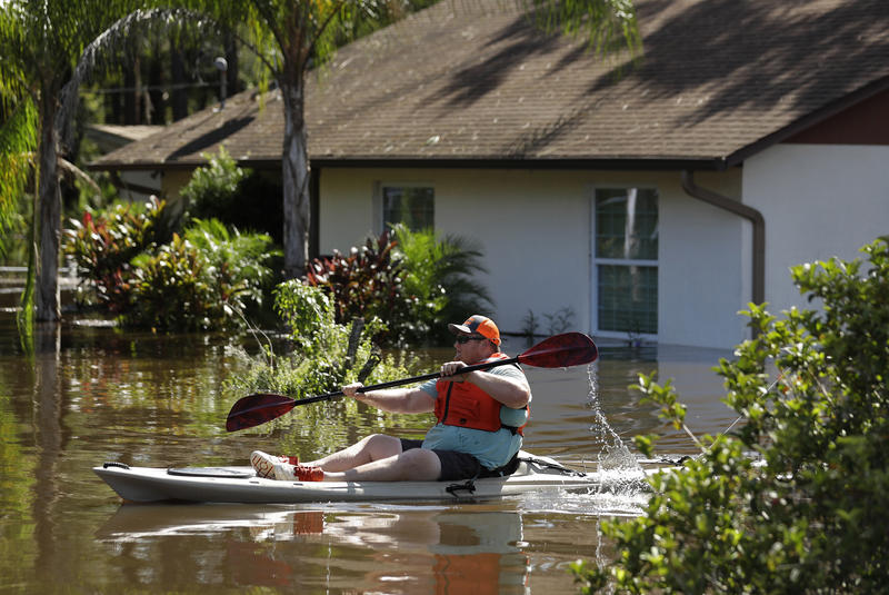 A man paddles a kayak near a flooded home along the Alafia River Tuesday, Sept. 12, 2017, in Lithia, Fla.