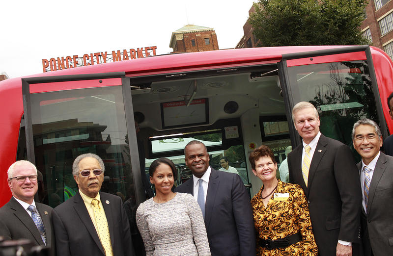 GDOT Commissioner Russell McMurry, Atlanta Council member C.T. Martin, Mayor Kasim Reed, Georgia Tech President Bud Peterson, Councilman Alex Wan and family members pose outside the self-driving shuttle.