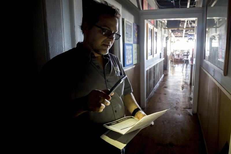 John Yarbrough, the owner of Spanky's restaurant on Tybee Island, uses the light from his cellphone to read paperwork Tuesday after storm surge from Irma knocked out power and flooded his restaurant. Many across Georgia lost power because of the storm.