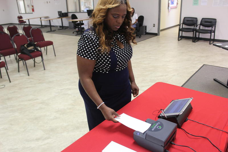 Rockdale County Elections Director Cynthia Welch uses a paper-ballot voting machine Georgia is testing as the state looks to potentially replace the electronic-only machines it uses now.