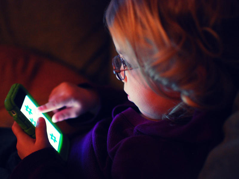 A young child plays with a touch screen phone.