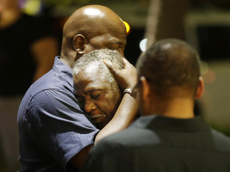 Worshippers embrace following a group prayer across the street from the scene of a shooting at Emanuel AME Church, Wednesday, June 17, 2015, in Charleston, S.C. A white man opened fire during a prayer meeting, killing multiple people.