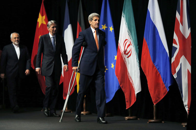 John Kerry, centre British Foreign Secretary Philip Hammond, centre and Iranian Foreign Minister Mohammad Javad Zarif arrive for a group picture at the Vienna International Center in Vienna, Austria, Tuesday, July 14, 2015. After 18 days of intense and of