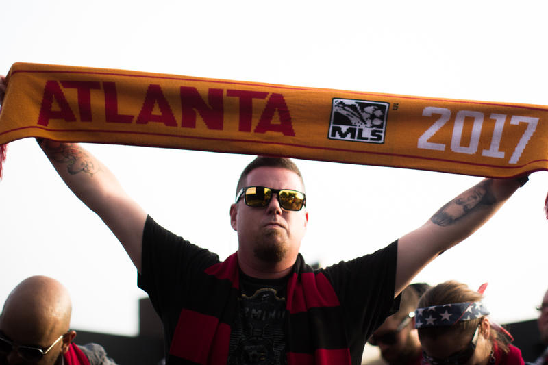 A fan holds a scarf during a party at which Atlanta United FC was announced as the name of an MLS soccer expansion team, Tuesday, July 7, 2015, in Atlanta. The team is scheduled to begin to play in 2017 at the city's new retractable-roof stadium.