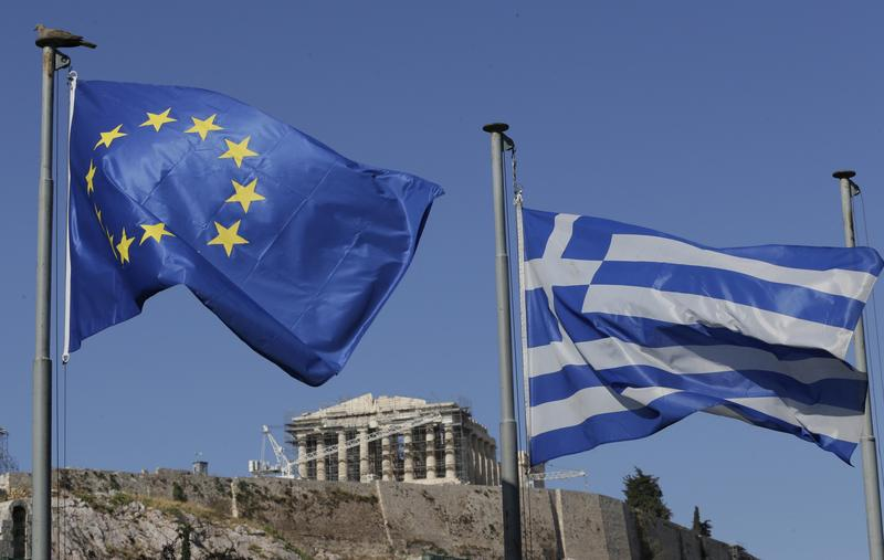 The Greek, right, and the European flags wave under the ancient Acropolis hill in Athens, Sunday, July 5, 2015. Greeks lined up at polling stations and ATMs alike Sunday as the country voted on its financial future