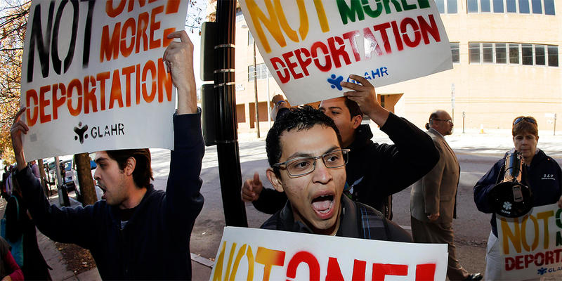 Immigration activists hold signs and shout during a protest in front of a building that houses federal immigration offices Tuesday, Nov. 19, 2013, in Atlanta. Eight activists, protesting deportations of people who are in the country illegally, were taken