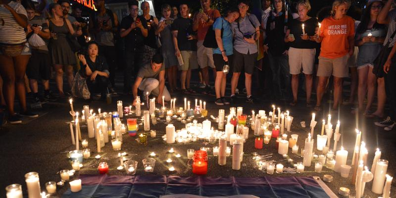 Participants gather around candles at a vigil honoring victims of a mass shooting in Orlando Florida