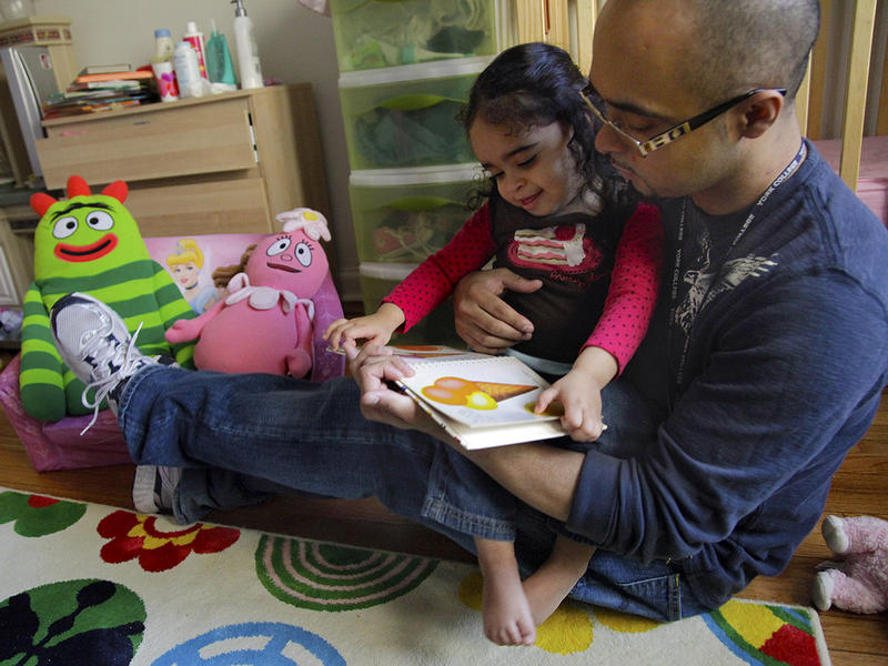 Christopher Astacio reads with his daughter Cristina, 2, recently diagnosed with a mild form of autism, in her bedroom on Wednesday, March 28, 2012 in New York. Autism cases are on the rise again, largely due to wider screening and better diagnosis.