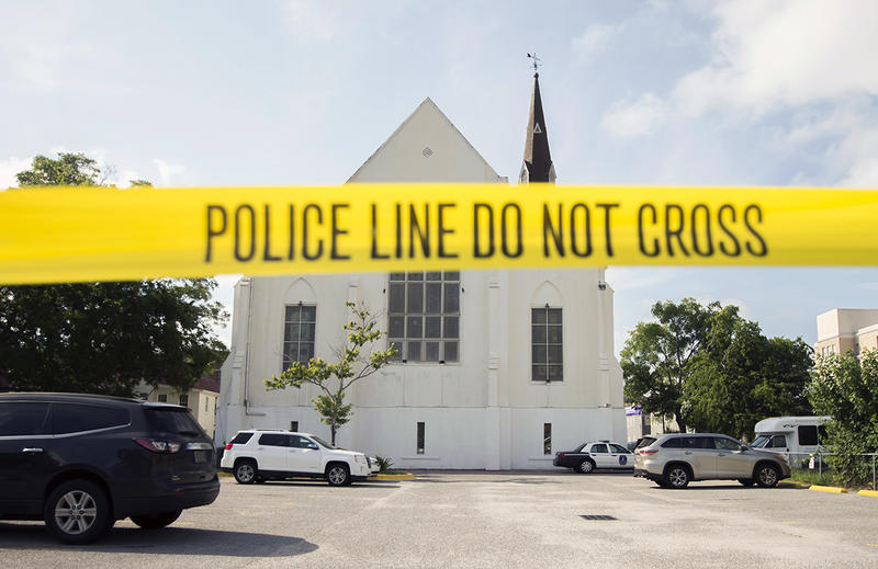 Police tape surrounds the parking lot behind the Emanuel AME Church as FBI forensic experts work the crime scene, Friday, June 19, 2015 in Charleston, S.C.