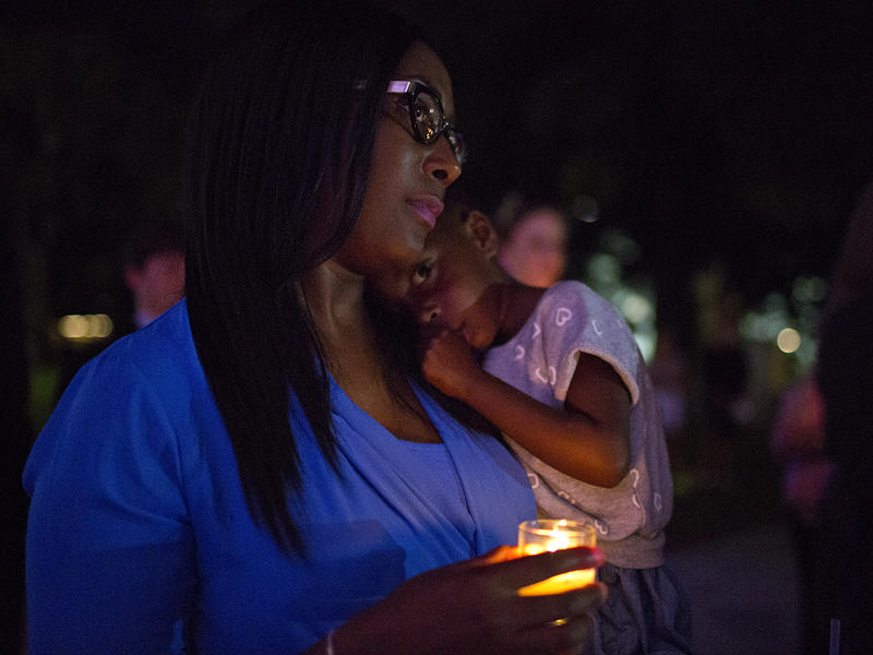 Brandy Taylor, left, holds her daughter Payton Taylor, 3, right, during a candlelight vigil to support Domestic Violence Awareness Month on Wednesday, Oct. 1, 2014, in Montgomery, Ala.