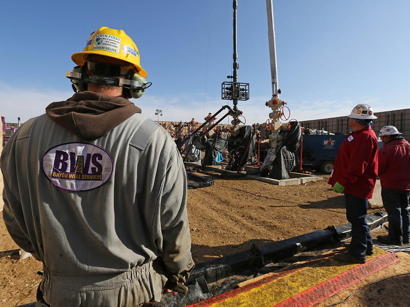 In this March 25, 2014 photo, workers keep an eye on well heads during a hydraulic fracturing operation at an Encana Corp. oil well, near Mead, Colo.