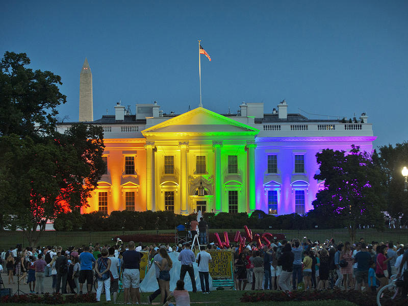 In this Friday, June 26, 2015 file photo, people gather in Lafayette Park to see the White House illuminated with rainbow colors in commemoration of the Supreme Court's ruling to legalize same-sex marriage in Washington.