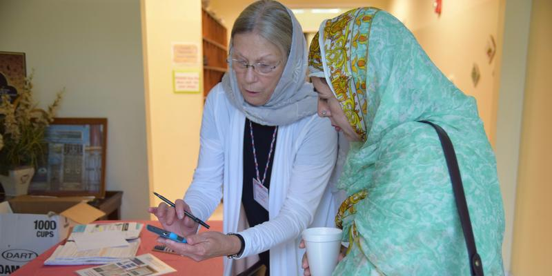 Naomi Binenfeld (left) uses her phone to show Tasneem Hayed how to check a voter's registration status