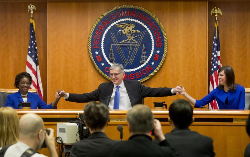 Federal Communication Commission (FCC) Chairman Tom Wheeler, center, joins hands with FCC Commissioners Mignon Clyburn, left, and Jessica Rosenworcel, before the start of their open hearing in Washington, Thursday, Feb. 26, 2015.