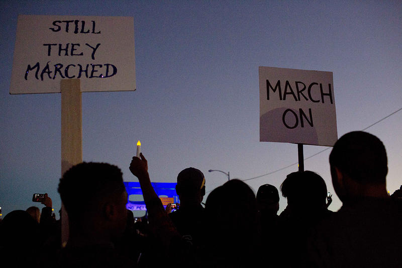 Marchers hold up a ''March On'' and ''Still They Marched'' signs as they make their way towards the Edmund Pettus Bridge in 2015.