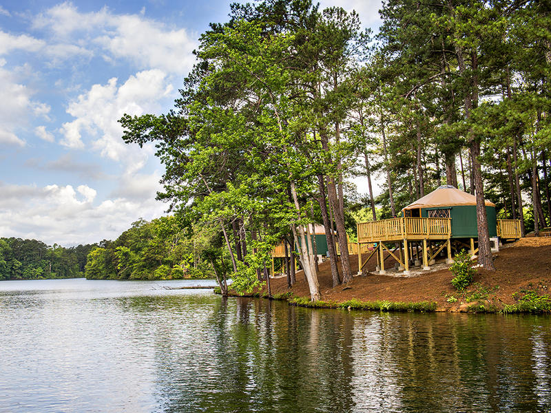 Yurts at Stone Mountain Campground, sitting peacefully at the lake's edge, can sleep up to five people and include log furniture, heating and air conditioning, electrical outlets, large windows, a skylight, a ceiling fan, and lockable doors.