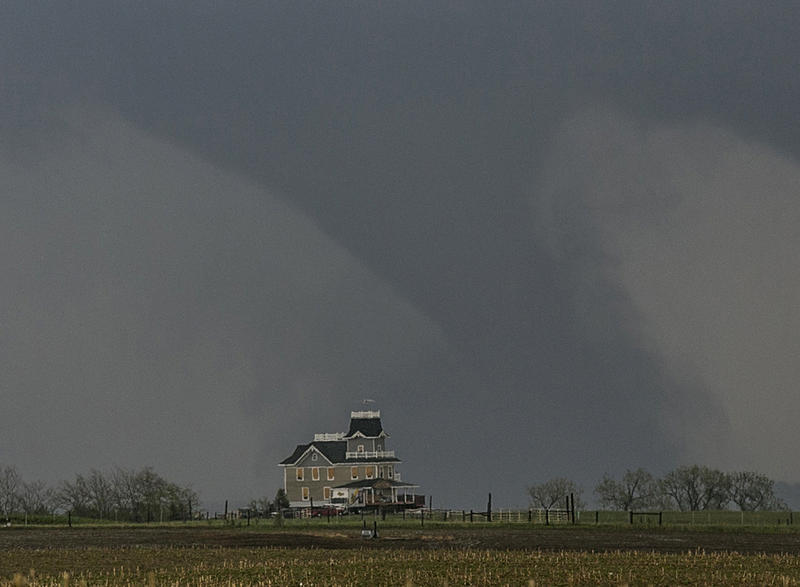 A tornado forms over a house near Pilger, Neb., Monday, June 16, 2014.