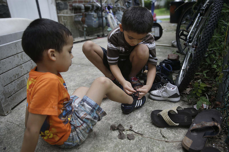In this July 17, 2014 photo, Kevin Torres, 7, right, helps his neighbor, Darwin Ruiz, 5, put his shoes on in Huntington Station, N.Y. Kevin arrived in the United States, unaccompanied, from El Salvador in May 2014.