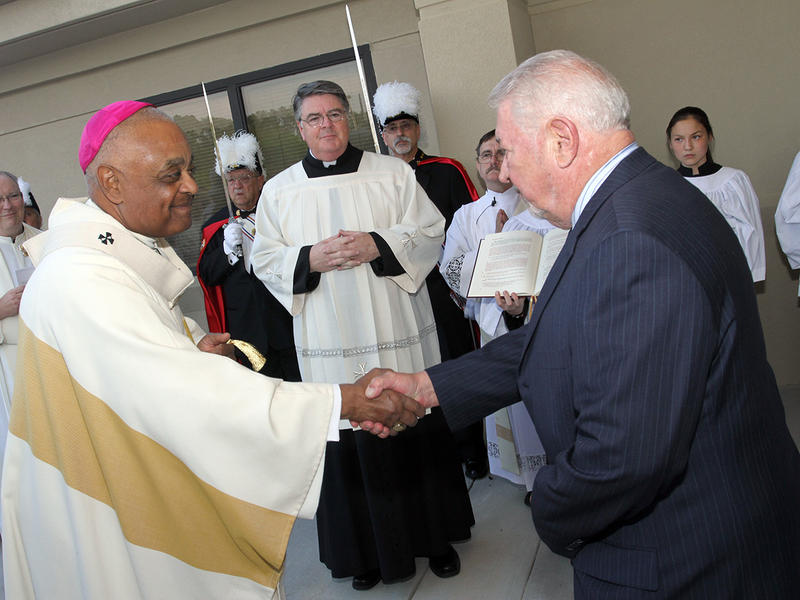 Standing before the doors of the church, Al Calsetta, right, chair of the parish council, shakes hands with Archbishop Wilton D. Gregory after handing over the keys of the church to him at the St. Francis of Assisi Church dedication.