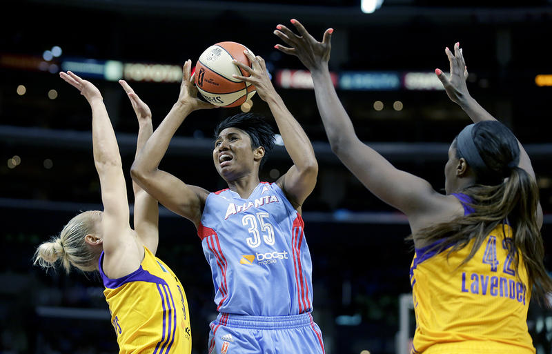 Atlanta Dream's Angel McCoughtry, middle, shoots between Los Angeles Sparks' Erin Phillips, left, and Jantel Lavender during the second half of an WNBA basketball game in Los Angeles, Thursday, July 16, 2015.