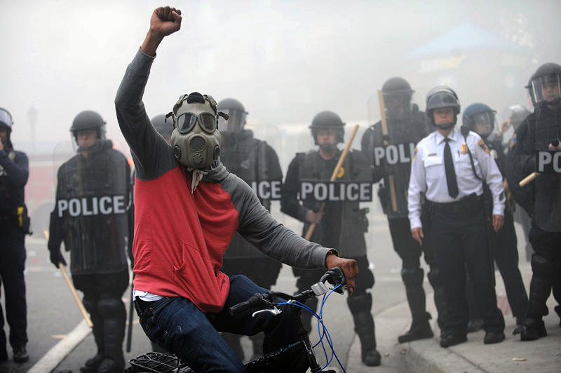A protestor rides his bike in front of a police line on April 27, the day of Freddie Gray's funeral. Riots and looting broke out throughout the city. Gray died in police custody on April 19th.