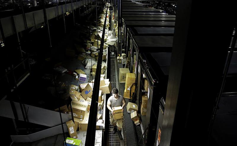 A worker carries a box while loading up trucks before deliveries at the United Parcel Service sorting facility in Roswell, Ga.