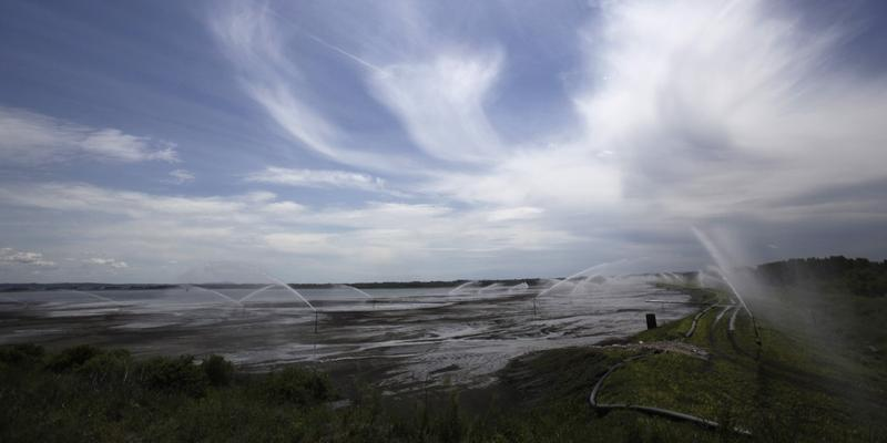 In this photo taken Tuesday, May 28, 2013, sprinklers watering coal ash landfill to limit dust, near the village of Usce, by the power plant Nikola Tesla, some 30 kilometers (19 miles) west of the Serbian capital Belgrade.