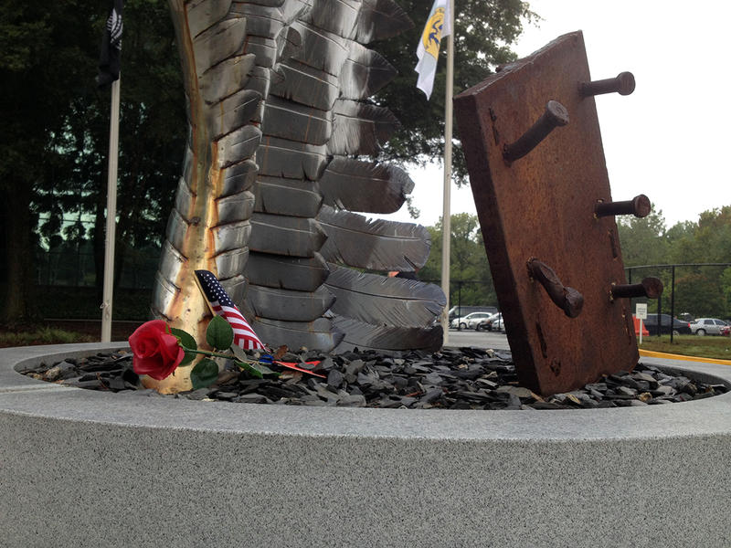 A rose and flag rest on the 9/11 memorial during DeKalb County's 9/11 commemoration.