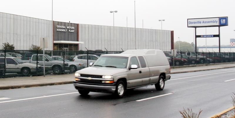 A pickup truck moves by the main entrance to the General Motors plant in Doraville, Ga. Monday November 21, 2005.