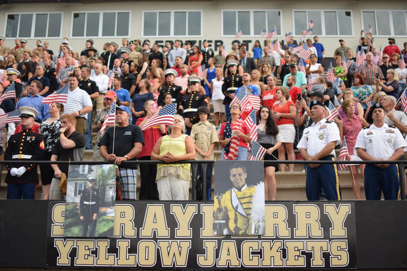 Crowds sing along to 'God Bless the U.S.A.'  during a vigil to celebrate the life of former Sprayberry High student Skip Wells.