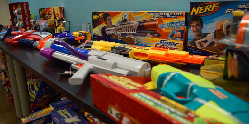 A display of many different versions of the Super Soaker on a table