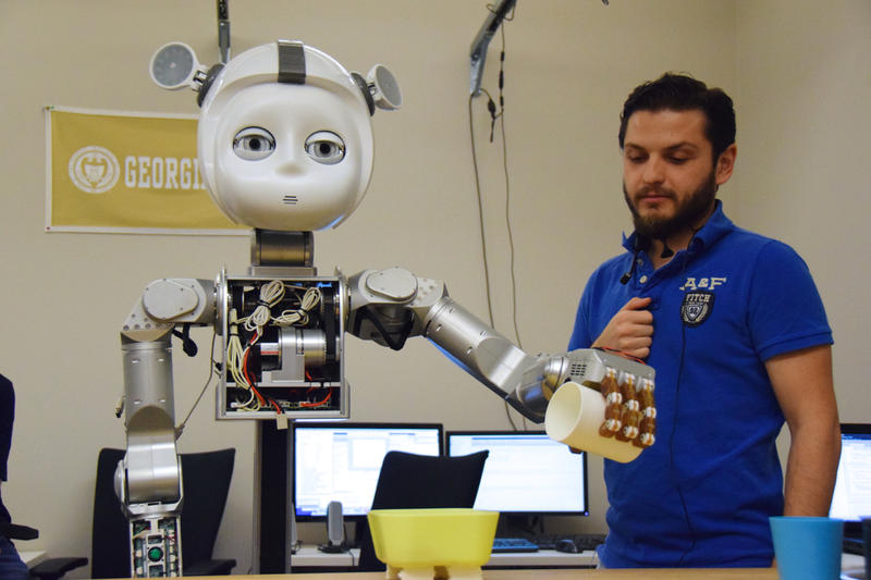 Georgia Tech Student Baris Akgun and robot 'Curi'. Students from around the metropolitan Atlanta area spent the day at Georgia Tech learning about robots as part of National Robotics Week. April 8, 2015