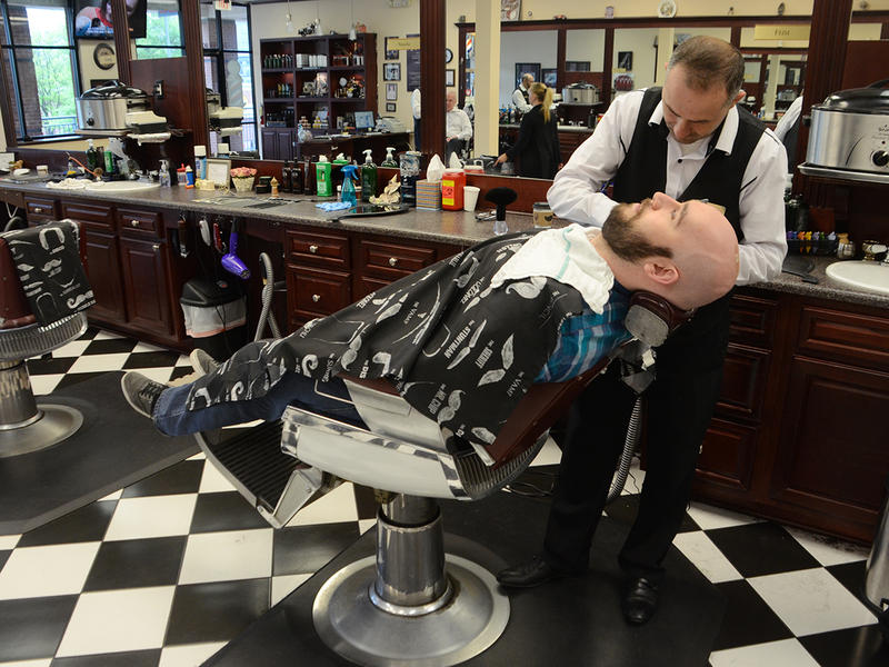 Dustin Farist gets a shave from Feim Krasniqi at Gino's Classic Barber Shoppe in Atlanta, Georgia on Thursday, April 16, 2015. Farist paid for his haircut in Bitcoin.