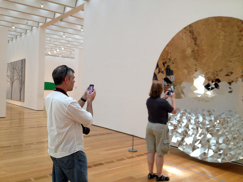 Visitors take photographs of an exhibit at the High Museum of Art