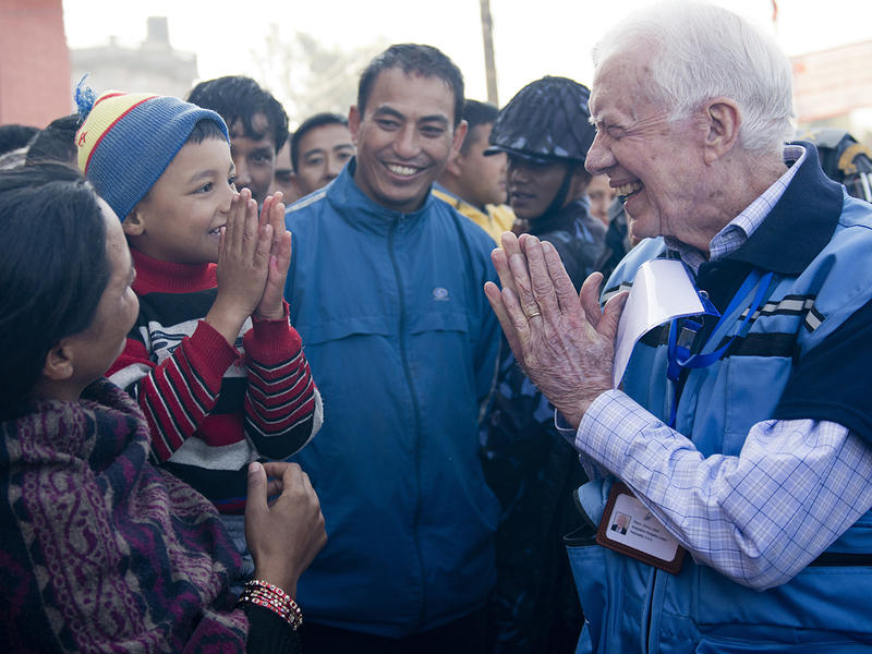 Jimmy Carter greets a young Nepali boy with the customary Namaste gesture during the Carter Center's observation of Nepal's constituent assembly elections in November 2013.