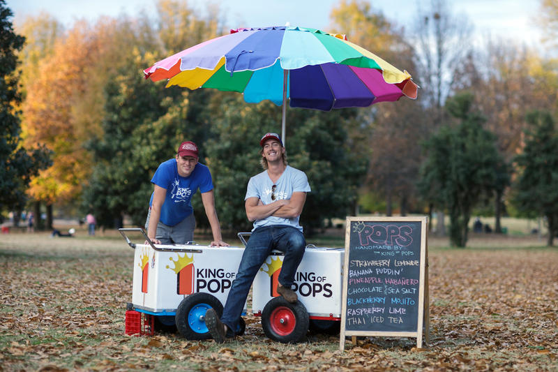 Steven Carse, Co-founder and CEO of King of Pops, left, and Nick Carse, Co-founder and CFO of King of Pops sit on King of Pops carts.