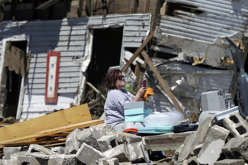 Sandra Hedrick looks at her mobile telephone as she sits in storm debris in Vilonia, Ark., Thursday, May 1, 2014.