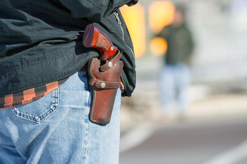 A man poses with his holstered gun exposed.