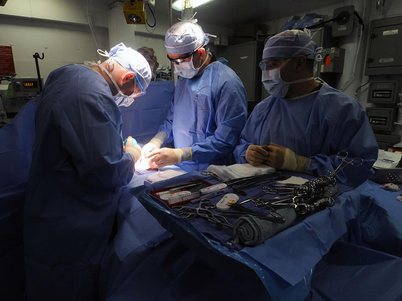 Lt. Matthew J. Bradley, left, and Lt. Cmdr. John R. Balentine, center, perform an umbilical hernia repair while Hospital Corpsman 3rd Class David L. Cumpian assists in the operating room aboard the aircraft carrier USS George H.W. Bush.