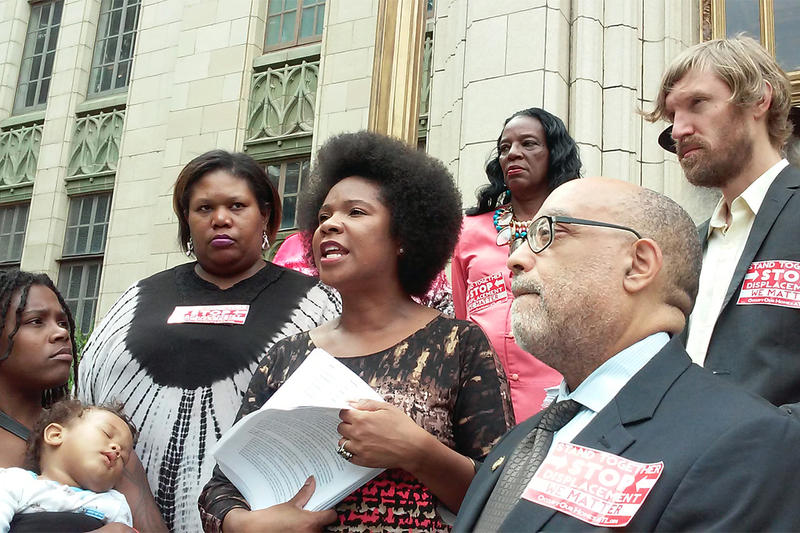 GSU Law Professor, Tanya Washington, center, speaks against the installation of a retention pond in the Peoplestown community at a protest on the steps of City Hall in Atlanta, Ga., on Sept., 21, 2015. Washington lives in one of the affected homes.